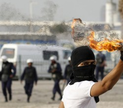 An anti-government protester throws a molotov cocktail at riot-police during clashes at the mourning procession of the murdered Ahmed Ismael Abdulsamad in the village of Salmabad